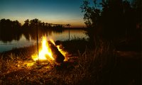 A beautiful sunrise by the river, a campfire, and birds singing