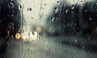 Running car in poring rain.