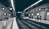Gentle rain, the train moving, passengers talking softly. Faint violin music drifts through the air.