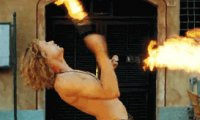 A scarred street performer breathes fire above the heads of a stunned crowd